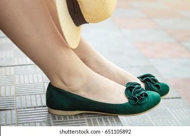 Female legs wearing green suede flats