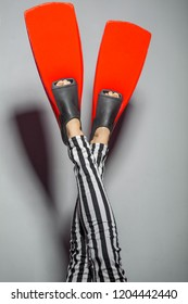 Female legs wearing red flippers and striped pants isolated over grey