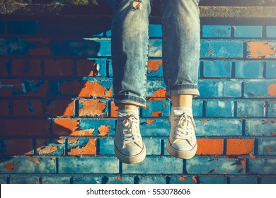 Female legs in white canvas sneakers and jeans dangling from a blue brick wall on a sunny summer day