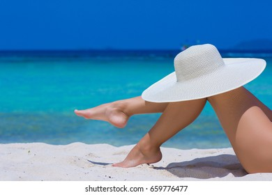 Female legs with white hat on the beach, blue sea and sky background