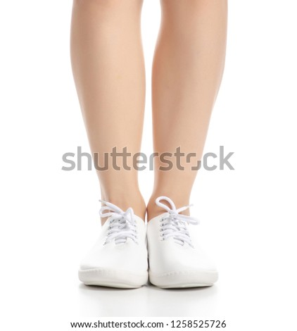 d1567ae96f Female legs in white sneakers shoes beauty on white background. Isolation