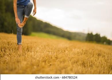 Female legs. Women barefoot in wheat field.