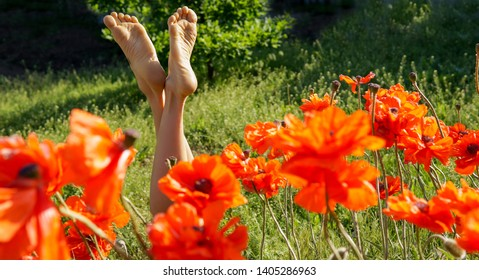 Female legs of young woman relaxing on a sunny meadow with red poppies
