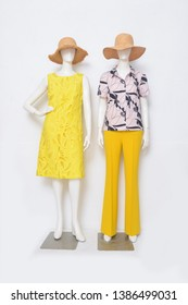 female in leopard pattern shirts , embroidered sundress , yellow sundress ,hat and yellow trousers , shoes, on full two mannequin isolated