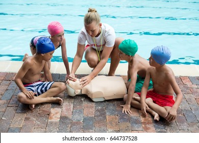 Female lifeguard giving rescue training to children at poolside