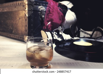 Female lingerie and accessories on vintage suitcase. Edited with faded colors and vintage effect. Shallow depth of field, focus on the glass of drink