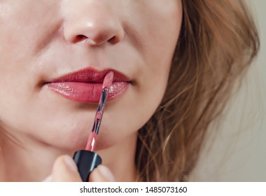 Female lips are painted with red lipstick, closeup. Women's health, cosmetics, sexuality