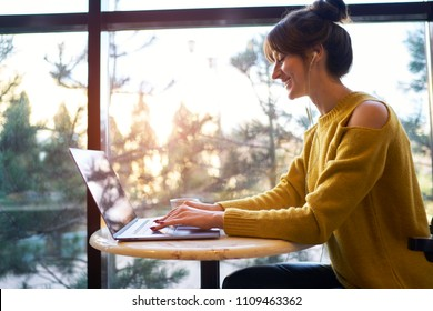 Female listening music on mobile phone during work on notebook. hipster girl using wifi in coworking space for making video call. Student preparing for exams searching information on netbook