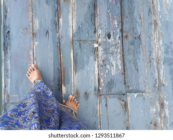A female with long sarong is walking bare foot on the old wooden floor with vintage finishing. The deck was built for an outdoor use. Photo shows blue tone both sarong & wood panels.