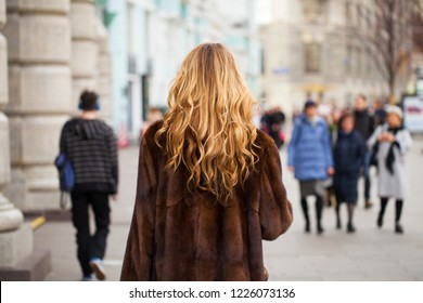 Female Long wavy blonde hair, rear view, autumn street outdoors