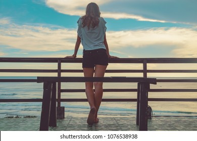Female looking at the distant ocean / sea view.