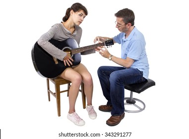 Female looking frustrated with male music instructor teaching how to play guitar.  The woman looks stressed out or unmotivated.  The guitar is generic and non branded.