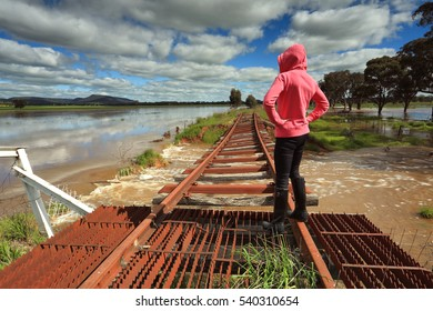 A female looks out over the floodwaters from the buckled train tracks at Crowther, Hilltops Region, Country NSW.