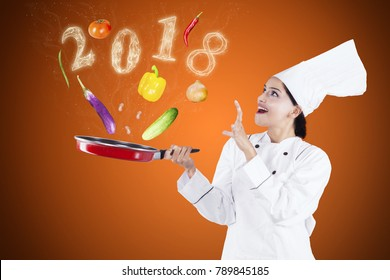 Female magician chef cooking on frying pan with food ingredients and smoke shaped of numbers 2018
