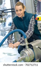 female maintenance worker examining brewery machine at brewery