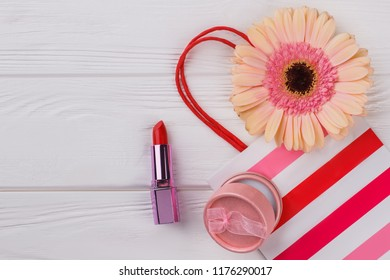 Female make up accessories. Multicolored gerber daisy flower, lipstic, powder and shopping bag. White wooden background.