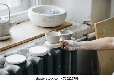 Female maker ceramics working with clay and putting bowls for drying on radiator. Pottery making, woman holding a bowl.