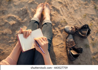 female makes notes and sitting on the beach; woman writes in diary and lying on sand;