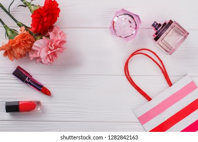 Female makeup accessories flat lay. Top view. Carnation flowers, lipstic, mascara, perfume and shopping bag. White wooden background.