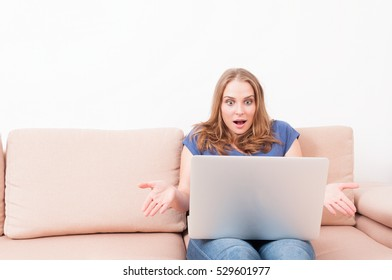 Female making amazed gesture holding laptop sitting on couch with copy text space