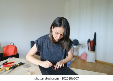 Female making black leather women bag. Girl likes handicraft and attending sewing circle. Lady with red manicure sitting near table with different instruments at workshop and fixing snap on pat