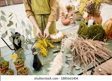 Female making compositions of dried and fresh flowers and herbs on the green table outdoors. Florist, gardener or decorator composing floral decoration concept. Close-up shot