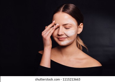 Female making peeling mask on face. Beauty, skin care, cosmetics and health concept. Facial treatment . Cosmetology and spa. Beautiful woman cleaning her face with a foam. Girl washing her face.