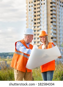 female male builders  helmets on  background of a house