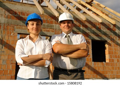 Female and male building designers wearing helmets posing over unfinished brick house with wooden roof structure