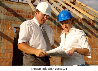 Female and male building engineers wearing helmets discussing building plans standing over unfinished brick house with wooden roof structure