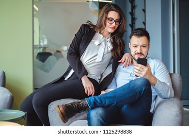 Female and male colleagues looking at mobile phone and smiling while sitting on the chair together