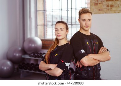 Female and male confident athletes with folded arms dressed in ems technology in gym with weight racks and stability balls in background