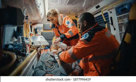 Female and Male EMS Paramedics Provide Medical Help to an Injured Patient on the Way to a Healthcare Hospital. Emergency Care Assistants Putting On Non-Invasive Ventilation Mask in an Ambulance.