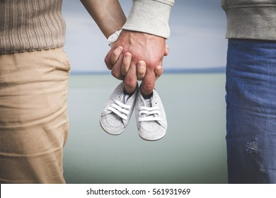 Female and male expecting a baby and holding each other hand with a small pair of shoes in there