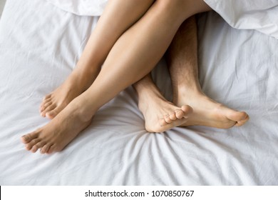 Female and male feet on soft comfortable bed mattress, sexy romantic couple relaxing together touching legs, lovers lying on white sheets resting enjoying intimacy in the morning, close up top view