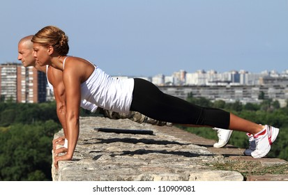 Female and male fitness instructors doing pushups on the top of the stone wall.
