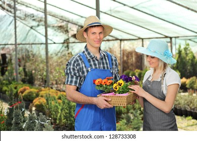 Female and male gardeners with a basket full of flower pots posing in a hothouse