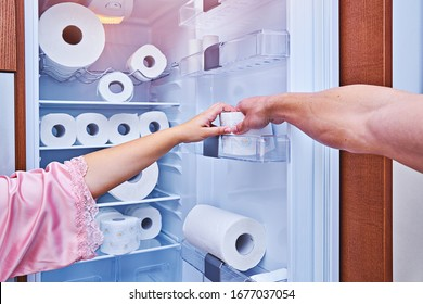 Female and male hand grab hold of last toilet paper roll on fridge door. Concept of over-buying toilet paper during coronavirus