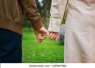 female and male hands holding hands