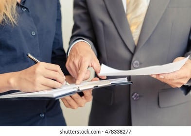 female and male hands pointing at document  discussing