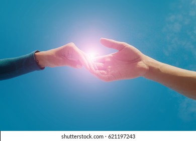 Female and male hands reaching to each other on sky background. Help and care concept. close up hand holding together on blur nature sky. Romantic moment. Healthcare concept idea. Intimate couple.