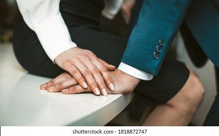 Female and male hands together. Close up shot. Passionate affair at office workplace. Woman wearing skirt sits at edge of office table. Man stands close to her. High quality photo.