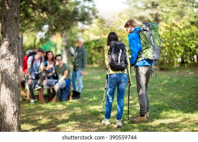 Female and male hikers with backpack in forest photographed from back