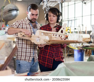 Female and male hobbyists engaged in creating plane models in aircraft workshop..