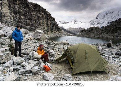 female and male mountain climber at base camp in the Andes in Peru with a tent and a small mountain lake during bad weather