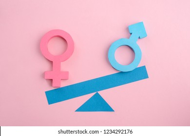 Female and male paper signs on scales over pink background. Gender inequality concept.