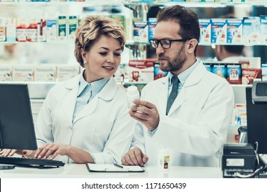 Female and Male Pharmacist Working in Drugstore. Two Pharmacist wearing White Coats looking at Bottle of Pills in Pharmacy. Pharmacist checking package of Medicine by using Computer