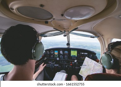 Female and male pilots are cooperating during flight on a small aircraft.