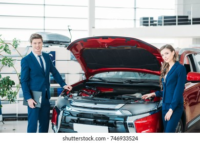 Female and male Sales managers of a car showroom standing near car with open hood