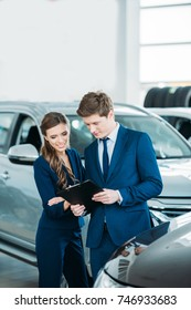Female and male Sales managers of a car showroom standing and looking at clipboard